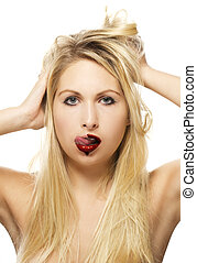 beautiful blonde woman licking chocolate from her lips on white background