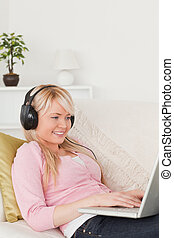 Beautiful blonde woman listening to music on her headphones while lying on a sofa in the living room