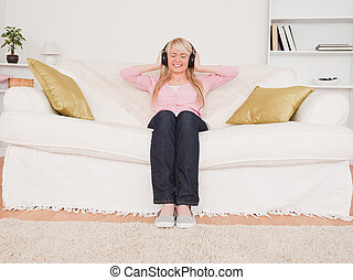 Beautiful blonde woman listening to music on her headphones while sitting on a sofa in the living room