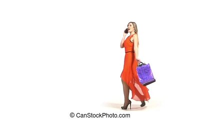 Beautiful blonde woman, long flipping hair in red dress with shopping bags talking on the phone, white background, slow motion