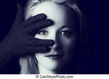 Beautiful blonde woman looking through fingers of black hand on her face artistic conversion