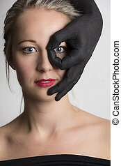 Beautiful blonde woman looking through fingers of a black hand on her face