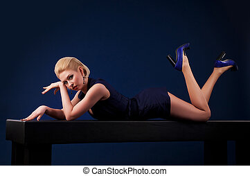 Beautiful blonde woman lying on a table
