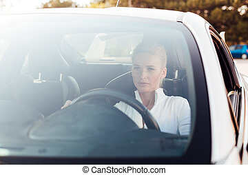 Beautiful blonde woman on the road driving a white car