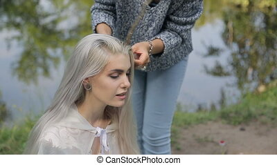 Beautiful blonde woman prepares for photoshoot in forest near lake.