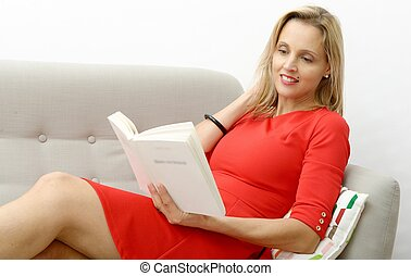 Beautiful blonde woman reads a book in the sofa