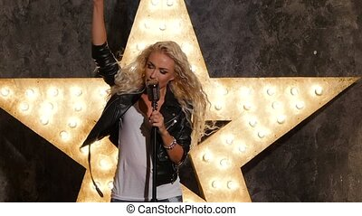 beautiful blonde woman singer with microphone, shining star in the background. slow motion