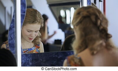 Beautiful blonde woman sits in front of mirror and talks with her friends.