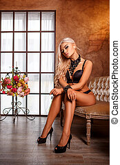 beautiful blonde woman sitting in black lingerie on the couch