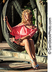 Beautiful Blonde Woman Sitting In The Park