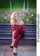 beautiful blonde woman sitting on a bench in the park