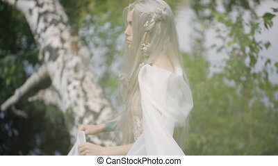 Beautiful blonde woman stands on birch above surface of lake.