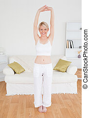 Beautiful blonde woman stretching in the living room