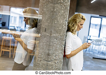 Beautiful blonde woman texting on phone