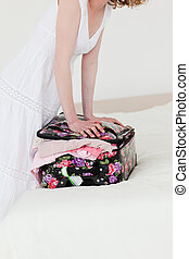 Beautiful blonde woman trying to close her suitcase