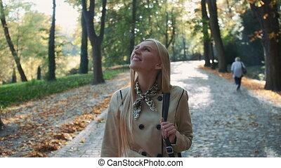 Beautiful blonde woman walking in the park in autumn