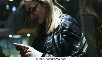 Beautiful blonde woman wearing glasses writing a message on her cell phone while going up in an elevator .