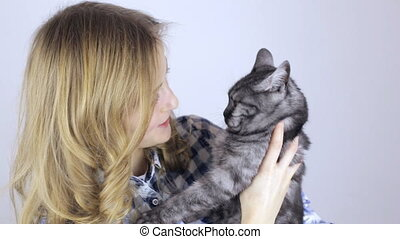 Beautiful blonde woman with a tabby british cat looking at camera