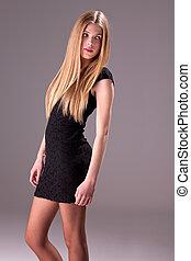 beautiful blonde woman with elegant black dress, studio shot