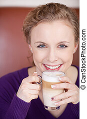 beautiful blonde woman with glass of latte macciato