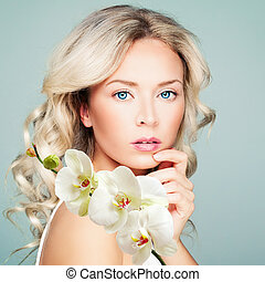 Beautiful blonde woman with healthy skin, wavy hair and white orchid flowers. Facial treatment, cosmetology, beauty, skin care and spa