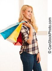 Beautiful blonde woman with long hari  holding shopping bags after purchase in a mall