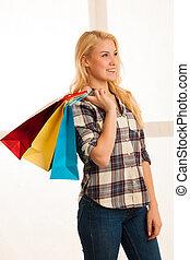 Beautiful blonde woman with long hari holding shopping bags...