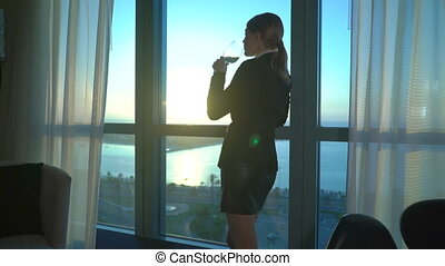 Beautiful blonde young business woman drinking wine and looking at sunset in the office, hotel room