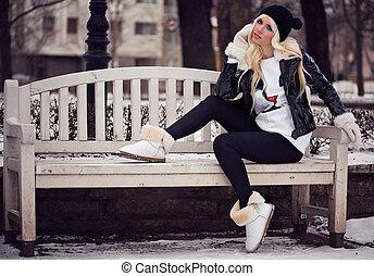 Beautiful blonde young girl in posing outdoors