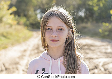 Beautiful blonde young girl with freckles outdoors on nature background in autumn, close up portrait