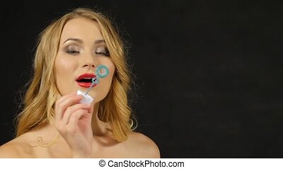 Beautiful blonde young woman blowing bubble on black, slow motion