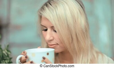 Beautiful, blonde young woman drinking tea in the garden