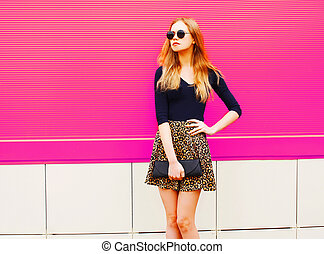 Beautiful blonde young woman in leopard skirt, sunglasses with handbag clutch posing on colorful pink wall background