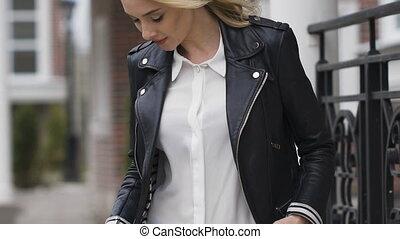 Beautiful blonde young woman in nice black coat. Posing
