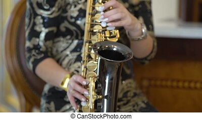 Beautiful blonde young woman is playing the saxophone. Sexy girl in golden black dress plays sax at home or party, sits on chair, practice, studying, learns songs