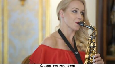 Beautiful blonde young woman is playing the saxophone. Sexy girl in red dress plays sax at home or party, sits on chair, practice, studying, learns songs