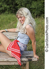 Beautiful blonde young woman sitting outdoors