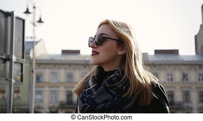 Beautiful  blonde young woman walking on the street