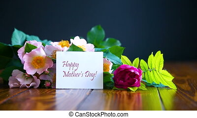 beautiful blooming roses and a greeting card for the mother