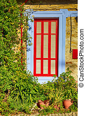 Beautiful blue and red window in mediterranean village house
