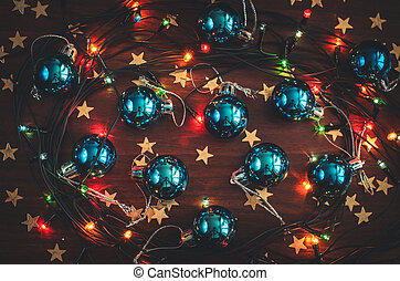 Beautiful blue christmas balls, golden star confetti and a glowing garland on the wooden table top view