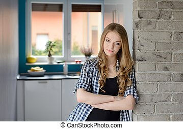 Beautiful blue-eyed blond woman rests on the wall in the kitchen.