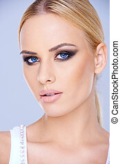 Beautiful blue-eyed woman wearing makeup