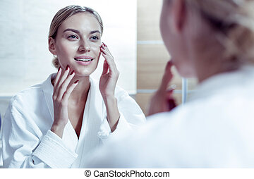 Beautiful blue-eyed woman with red nails touching her face after using cream