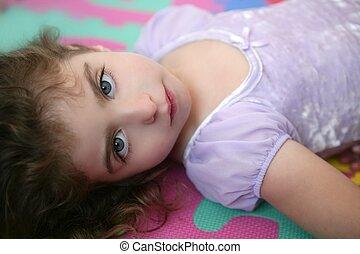 Beautiful blue eyes little girl lying on floor