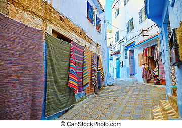 Many colorful Moroccan carpets for sale on a street in Medina of Chefchaouen, Morocco, small town in northwest Morocco known for its blue buildings