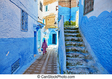 Moroccan woman in traditional clothes (jellaba) walking on a street in Medina of Chefchaouen, Morocco, small town in northwest Morocco known for its blue buildings