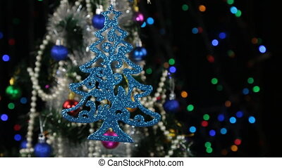 Beautiful blue New Year and Christmas decorations in the shape of a Christmas tree swinging on a rope