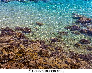 Beautiful blue shallow sea water near the rocky shore