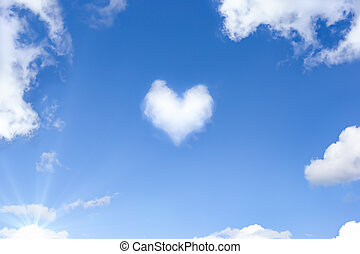 Beautiful blue sky with a white cloud in the shape of a heart. Natural background with a copy space